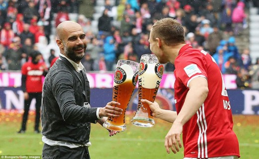 The outgoing head coach celebrates his side's success with Bayern Munich player Holger Badstuber