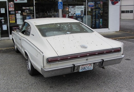 A white Dodge Charger covered in bird poop.