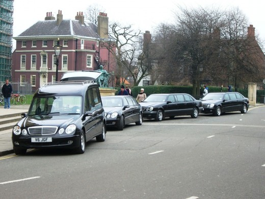 A hearse leading a funeral procession in modern times. Many superstitions surround the hearse.