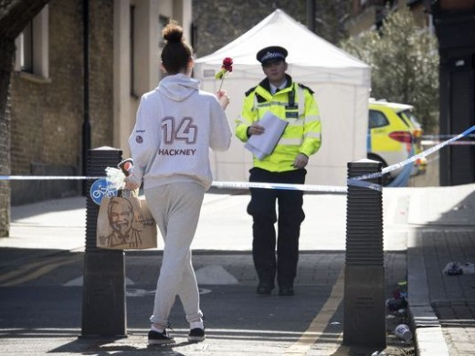 A flower is taken to the scene of one of the stabbings in Link Street, Hackney