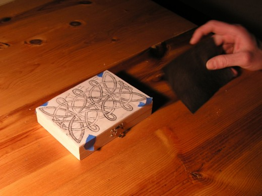 The carbon paper goes between the sketch and the wood.