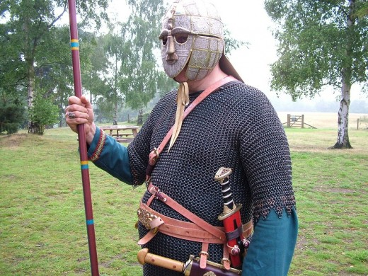 An actor displays replicas of grave goods from the Sutton Hoo ship-burial: helmet, belt buckle,and sword.