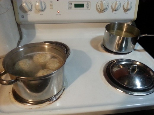 Matzo balls cooking in water, while the pan of chicken broth waits