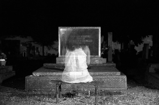 Ghost Woman in front of a Graveyard Headstone