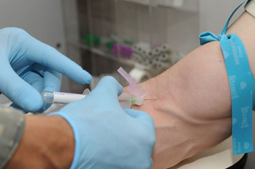 Blood for testing is drawn using a syringe and needle.