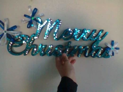 Light and dark blue sequence and ribbon Christmas sign.