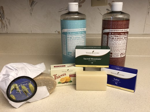 Bronner's Castile liquid soap, Young Living bar soaps, and Wildernss Family coconut oil-based oatmeal soap