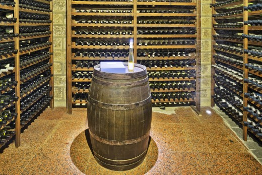 Vintage-style cellar with stone tiles and re-purposed wine barrel for a table.