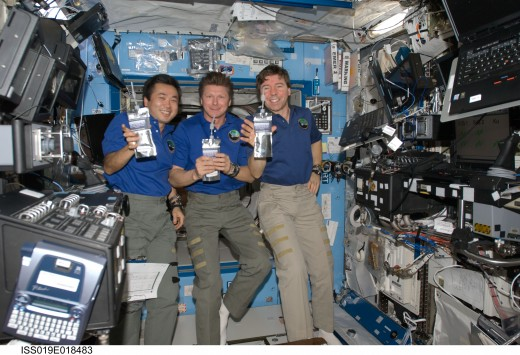 Expedition 19 Commander Gennady Padalka (center) and Flight Engineers Mike Barratt (right) and Koichi Wakata, holding drink bags with special commemorative labels in the Destiny laboratory.