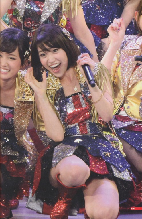 Atsuko Maeda is seen here in the background during a LIVE performance with Yuko Oshima (center).