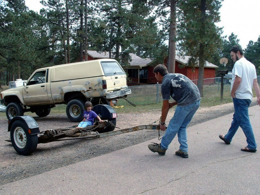 Child sitting on a tow dolly.  A motorhome can use a tow dolly to pull a front-wheel drive vehicle that must have one end off of the ground.