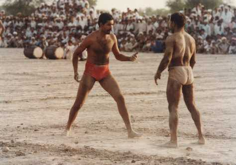 Two competitors in Kabaddi, which is a team sport, face off at a match being played in Burewala, district Vehari of Punjab.