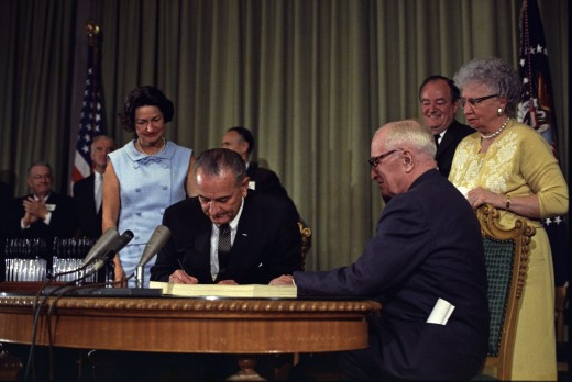 July 30, 1965, Lyndon B. Johnson signing the Medicare Bill in Lamar, Missouri. Harry Truman seated at the table, Lady Bird Johnson in blue, Bess Truman in yellow.