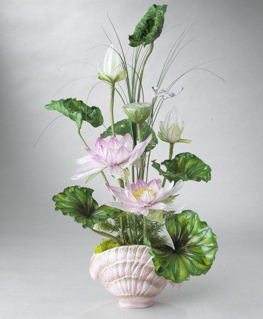A simple leaf spiral design of leaves with pink flowers arranged in a graduated vertical pattern in a shell-shaped vase.