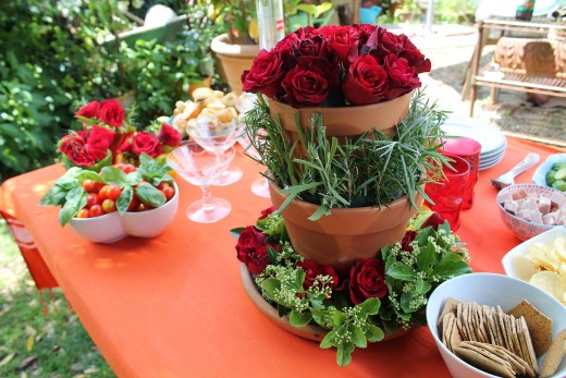 "Clean plastic vases with artificial red roses are clean and worry free on a dining table. Do you see the letter ""I"" in this arrangement?"