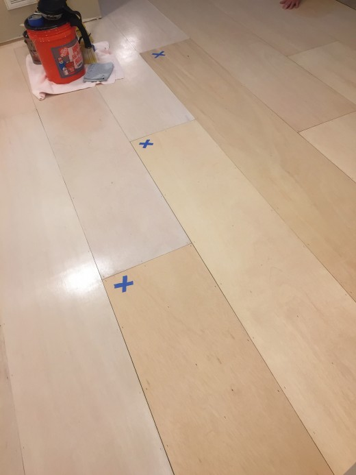 The largest space had to be done in sections. This pic shows the white washed floor planks against the natural wood. Taped Xs marked where we stopped to let paint /poly dry...