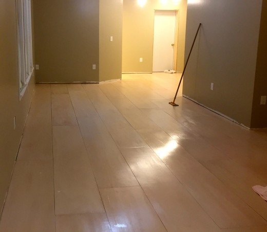 A little sanding was needed before final coat, then we cleaned it carefully. A pole sander was huge help. (Sorry for the poor lighting.)  This is when Mr. Brilliant applied the dark caulk to all seams. See the great look for the light floors below.