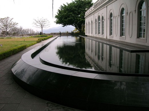 The main building is surrounded by a tranquil pool that reflects the museum wall.