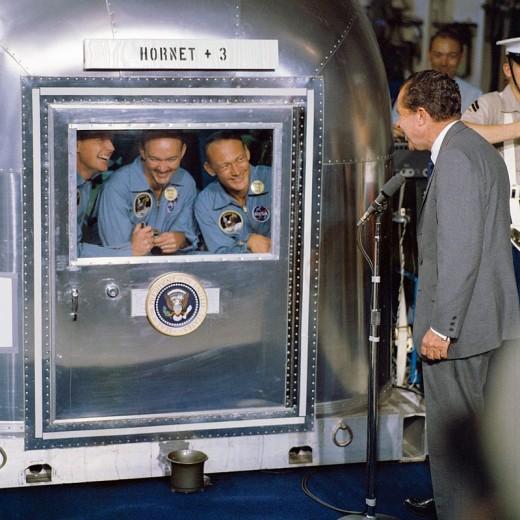 President Nixon talks the three astronauts of Apollo 11 in the quarantine trailer.