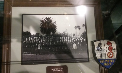 The USS Pueblo exhibit at the National Cryptologic Museum in Maryland includes a picture of the crew and the ship's emblem.  October 2018.