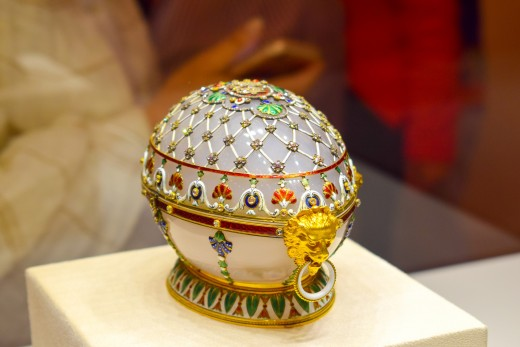 A Faberge egg decorated with a net of assorted bead work. A gold lion's head with a loop accents the point of the egg.