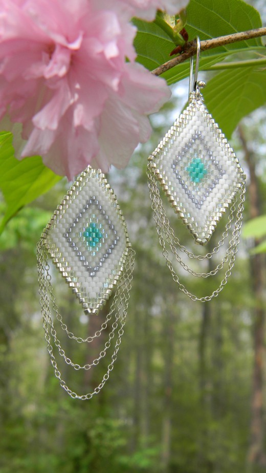 A pair of square canvas earrings beaded with seed beads and finalized with silver chain.