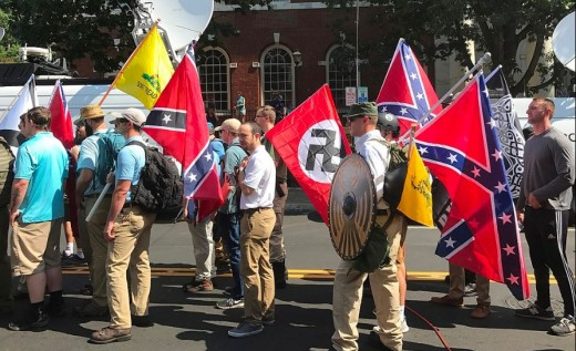 """Unite the Right"" participants preparing to enter Emancipation Park in Charlottesville, Virginia on August 12, 2017. They carry Confederate battle flags, Gadsden flags and a Nazi flag."