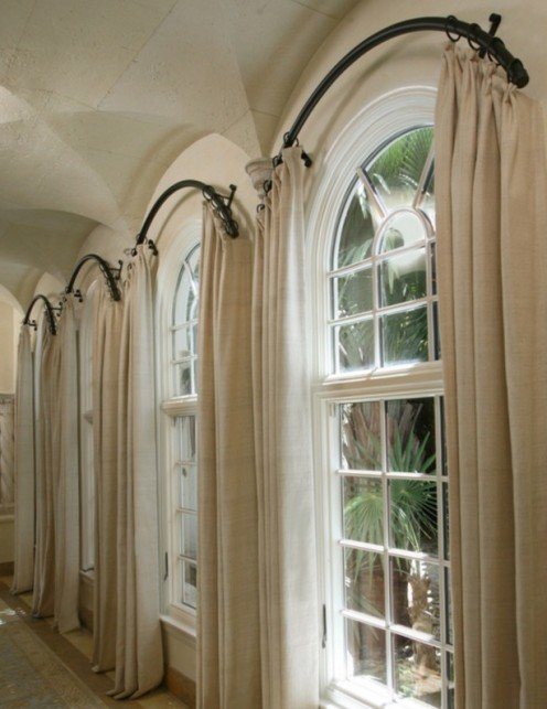 Curved curtain rods installed outside of the arch creates a striking look.