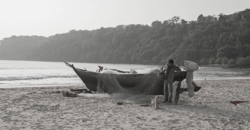 Fisherman tending to his nets and fishing boat on Agonda Beach