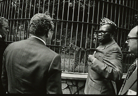 Mobuto Sese Seko, former dictator of Zaire (now the Democratic Republic of the Congo), showing guests caged leopards kept on the grounds of his palace.