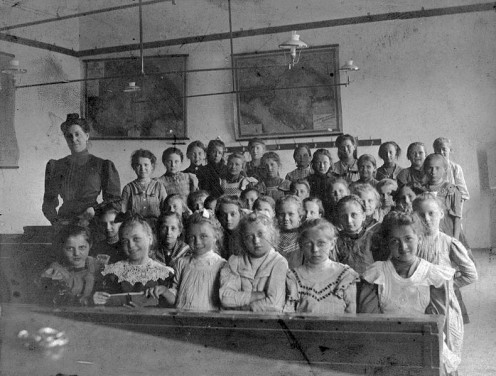 1908 classroom with teacher and children all sitting still and showing respect.