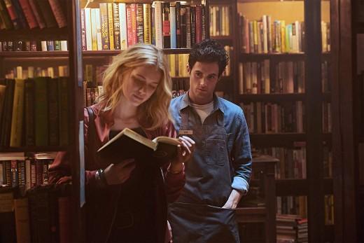 Guinevere Beck (Elizabeth Lail) reading while Joe Goldberg (Penn Badgley) stares intensely.