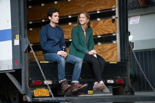 Joe (Penn Badgley) and Beck (Elizabeth Lail) sitting outside a large moving truck.