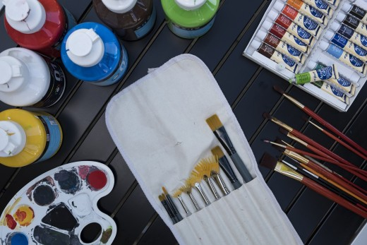 A table display of tubes and bottles of acrylic paints, and a pocket holder of synthetic brushes.
