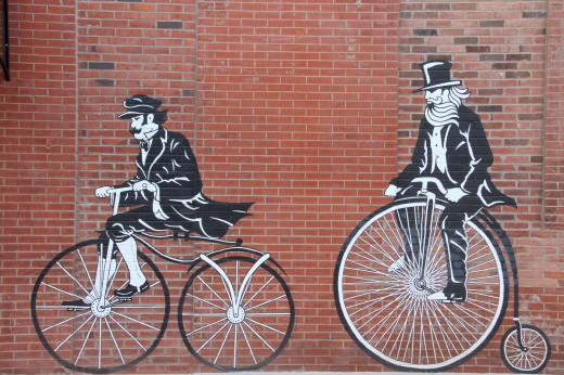 Two male bicyclist painted on a red brick wall of a building.