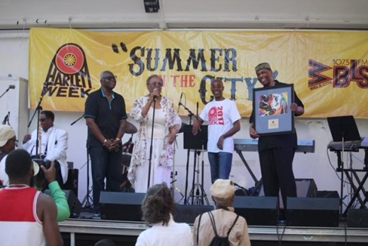 (L-R) Voza Rivers, Nana Camille Yarbrough Marko Nobles and Imhotep Gary Byrd (holding award) with the Jeff Foxx Band in (background)