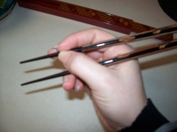 Don't hold the chopsticks so close to the front.  See how it doesn't give you much range of motion?
