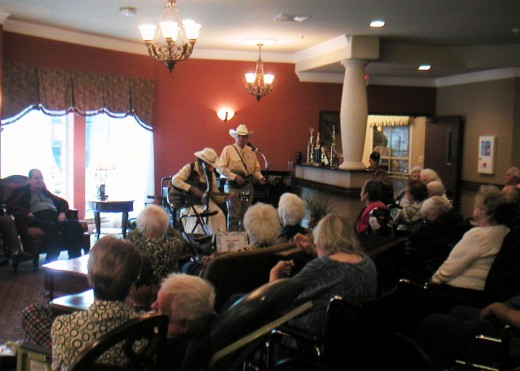 "Musicians, Sam and Pat with ""Two-R-More,"" visit and entertain the guests."