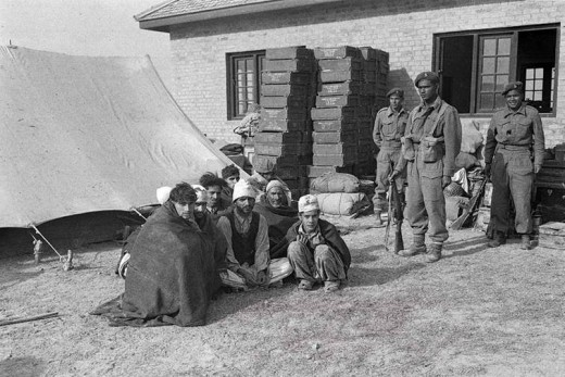 Captured Pakistan tribesmen being guarded  by Indian soldiers