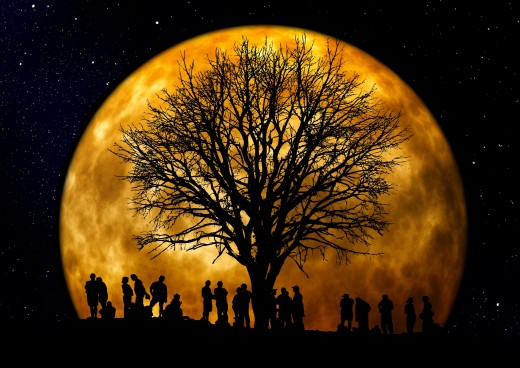 Huge moon with tree and people. Possibly a Harvest moon? Certainly a Super Moon.