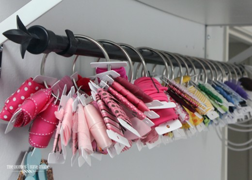 Another way to store ribbon is to use space in your closet. This idea uses a curtain rod and rings to store ribbon. You can organize by color and see exactly what you have. And it is pretty too/