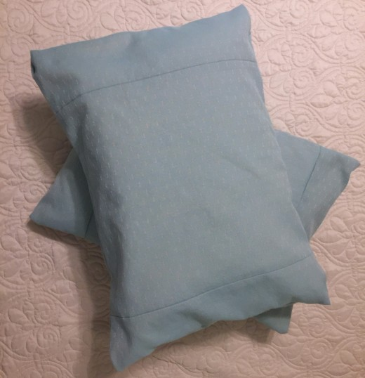 Two pillows created from one bed pillow covered with washable polyester envelope covers. The weight and weave of this fabric gives a prized textured look to an inexpensive product.