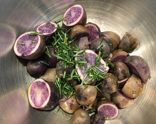 Purple potatoes with rosemary getting ready to roast
