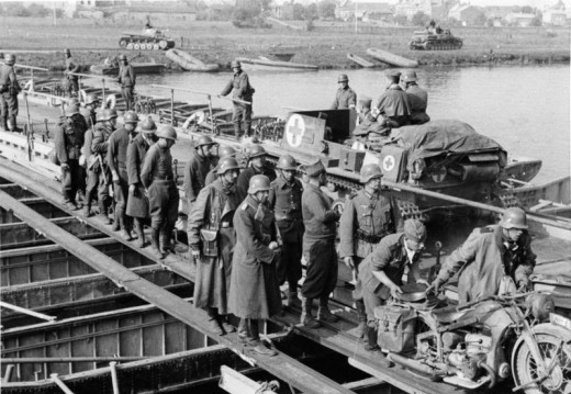 French prisoners march to the rear while German troops cross pontoon bridges at Sedan.