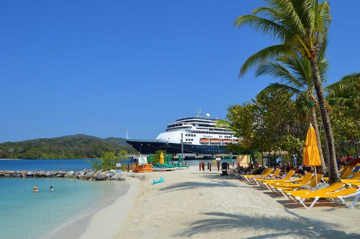 A cruise ship sits in the harbor just beyond Mahogany Bay Beach.