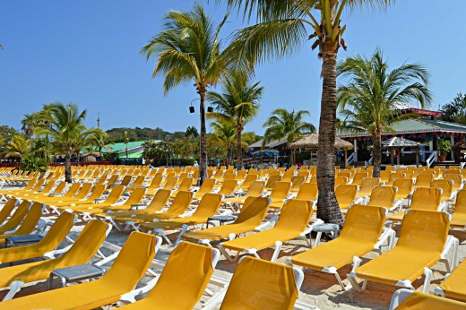 Hundreds of lounge chairs line the beach with a restaurant in the background.
