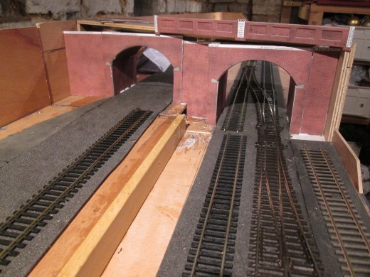 The view down onto the viaduct shows the brick front wall fixed in place. Where the pointwork starts on this side is Unit 2. There will be a right-hand point on the upper level to take the depot track off the main running lines