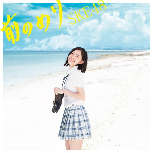 Singer Jurina Matsui at a beach in Okinawa, Japan smiling and holding a pair of shoes.