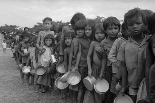 Refugee children wait for food outside Phnom Penh