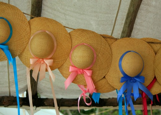 Large brim straw hats with colorful ribbons.